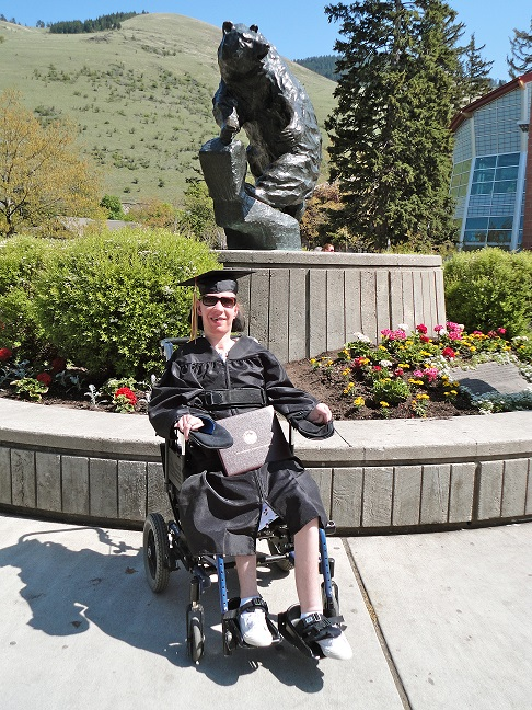 Sierra in graduation cap and gown in front of grizzly statue on UM campus