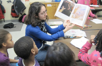 Sara Mann, School Age Program Group Leader, leads students in a directed reading.