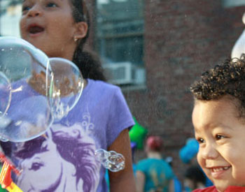 Children at East End House's Annual Summer Block Party enjoy bubbles at one of the activity tables.