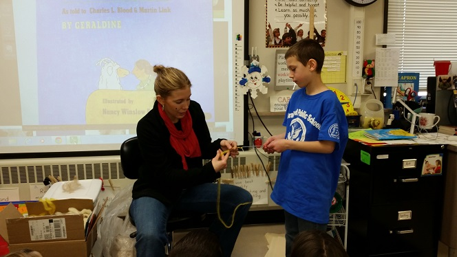 Carrie Allord helps a student create a wook bracelet