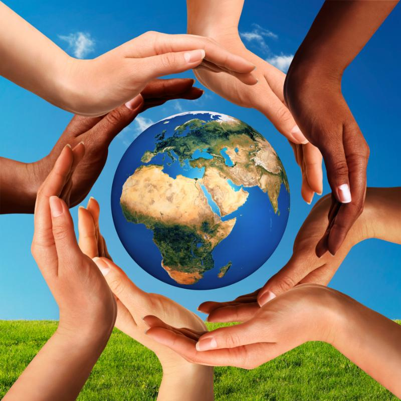 Conceptual peace and cultural diversity symbol of multiracial hands making a circle together around the world the Earth globe on blue sky and green grass background.