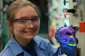 MIT chemistry graduate student A. Jolene Mork holds bottles of fluorescent quantum dots.