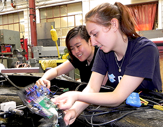 Michelle Chao and Rose Abramson work on steering wheel electronics panel.