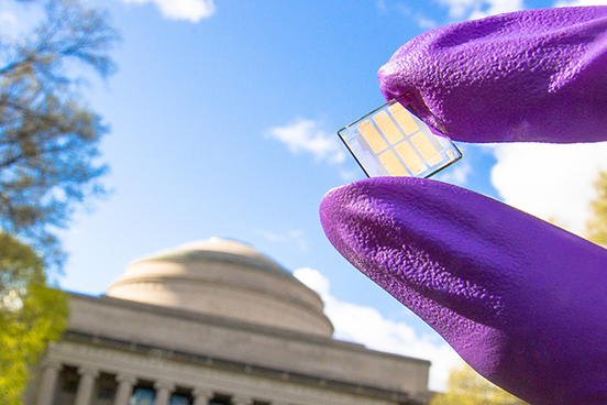 Researcher displays a sample of the record-setting new solar cell on the MIT campus.  Photo courtesy of Chia-Hao Chuang