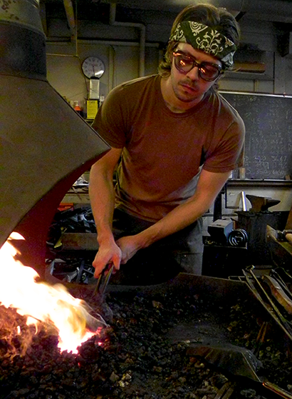 Graduate student James Hunter heats a metal blade in hot coals.