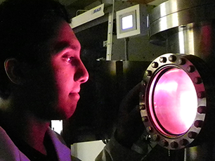 Rahul Kini peers into an electron sputtering machine used to create thin film batteries in the lab of Professor Carl V. Thompson. The faint glow comes from plasma in the sputtering process. Photo, Denis Paiste