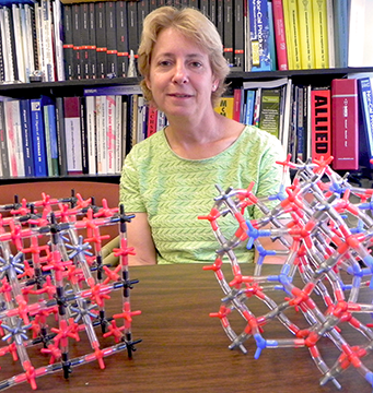 Caroline Ross, Toyota Professor of Materials Science and Engineering at MIT, with models demonstrating the crystal structures of complex metal oxides.