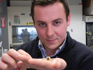 Thomas Crouzier holds a gold-coated quartz crystal microbalance which is used in a fluorescent microscope to measure the watery content of coatings on natural and modified pig gastric mucin.