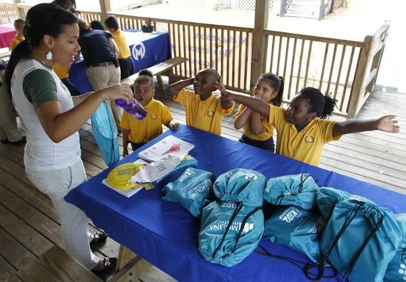 children receiving On The Move backpacks.