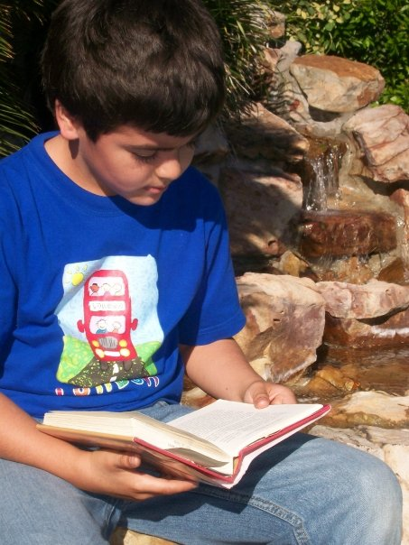 Antonio reading a book by the brook.