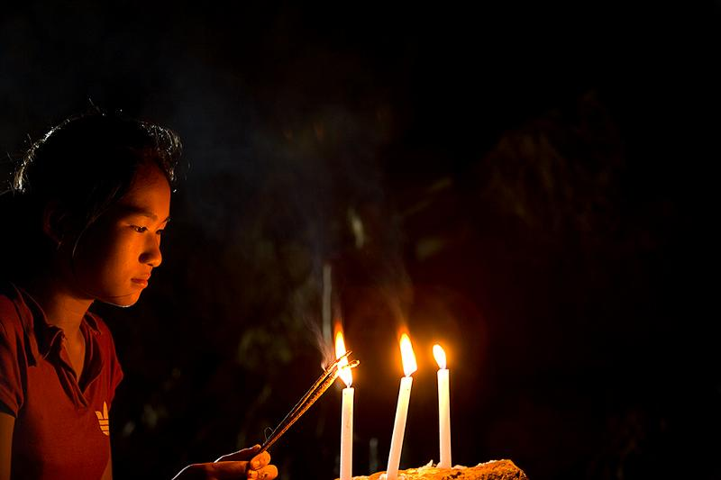 Lighting candles in Tham Piu Cave