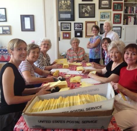 Volunteers help prepare the newsletter for mailing.