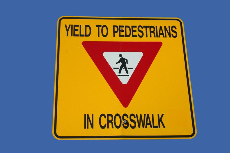 yield to pedestrians in crosswalk bright yellow sign