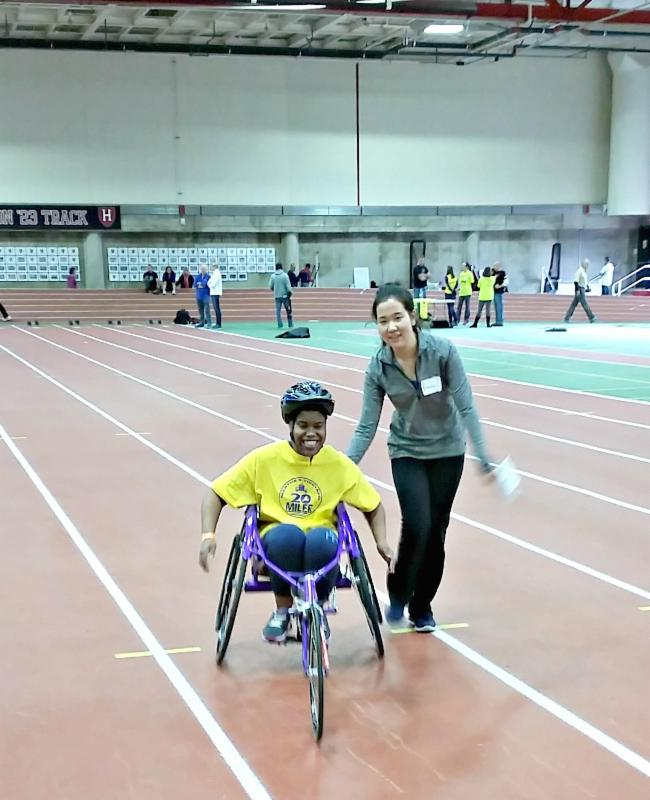 A Junior Team With A Vision member wheelchair racing on a track with the help of a Delta Gamma volunteer