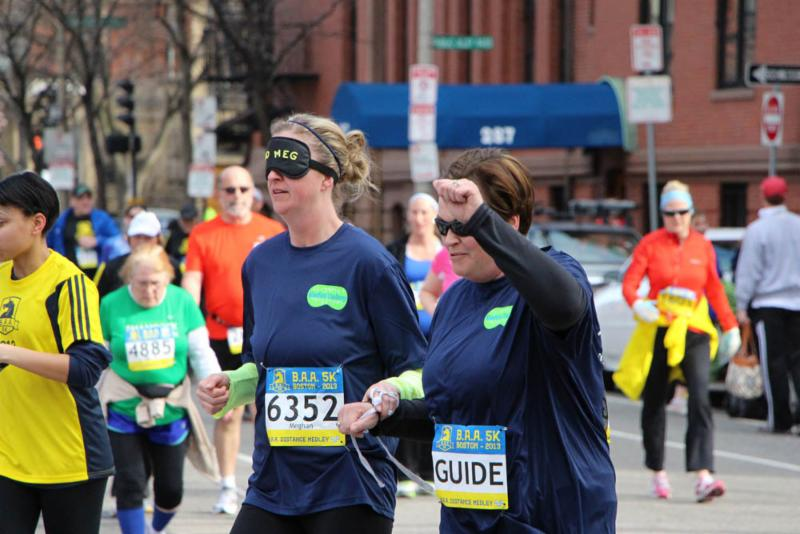 A woman guides a blindfolded woman as they run together as part of the Blindfold Challenge