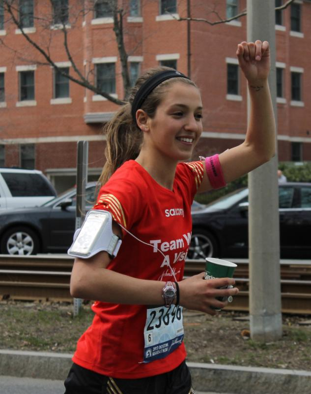 A girl representing Team WIth A Vision runs in the Boston Marathon, smiling and pumping her fist in the air