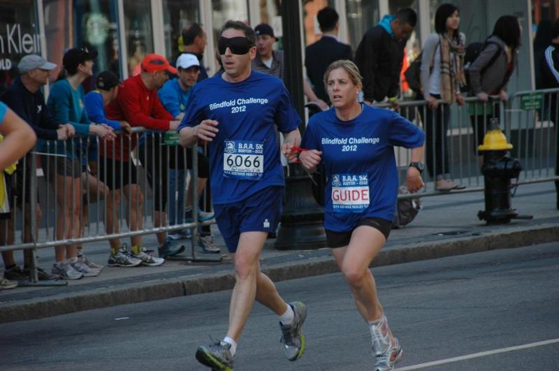A blindfolded runner and guide run tethered at the B.A.A. 5K