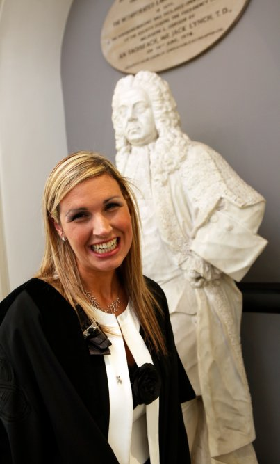 Sinead Kane wearing a robe at her graduation as a solicitor, standing in front of a statue