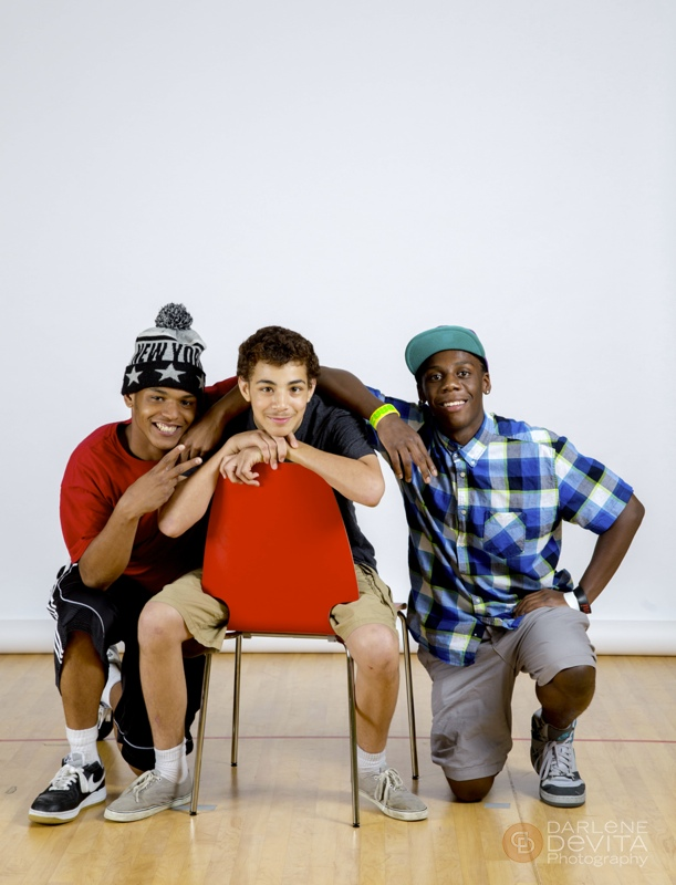 Three Ivy Street students pose for the camera in front of a white background
