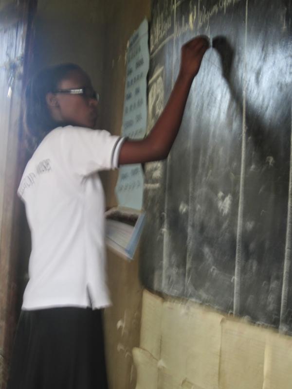 teacher writing on a blackboard with chalk