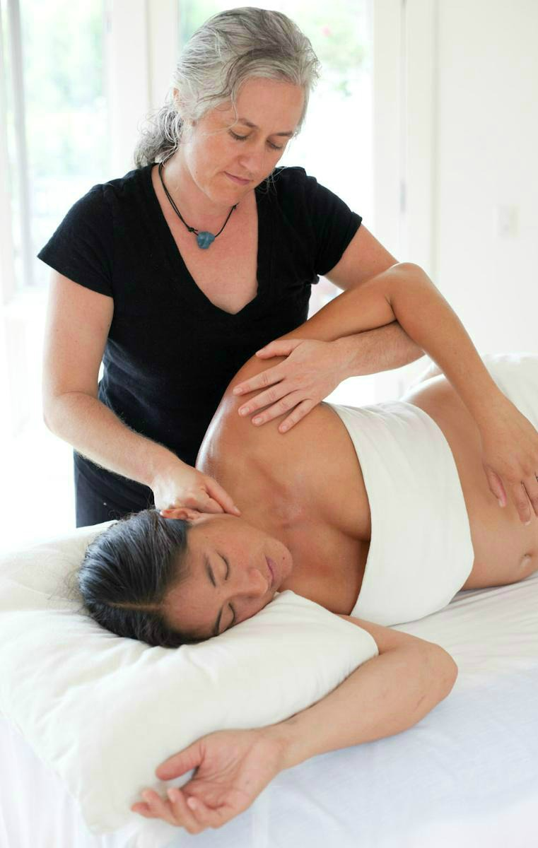 sidelying woman receiving shoulder massage 2