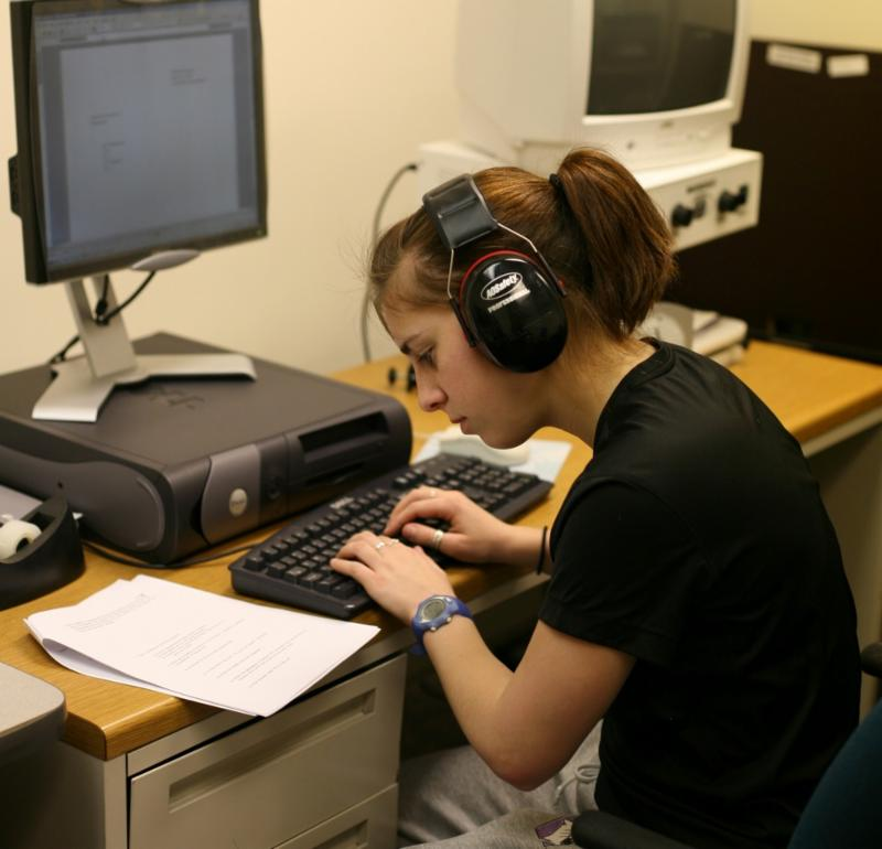 young girl sitting at a computer wearing headphones and looking at a piece of paper while typing