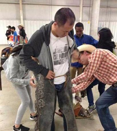An international student tries on rodeo chaps