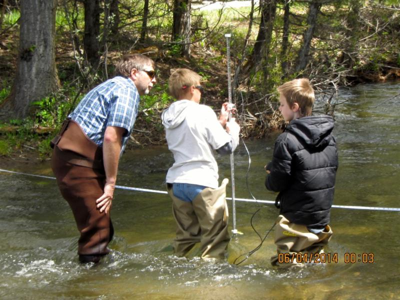 George Liknes, a Helena Forest fisheries biologist and volunteer on the project helps students from the Lincoln School collect stream flow information on Poorman Creek near Lincoln.
